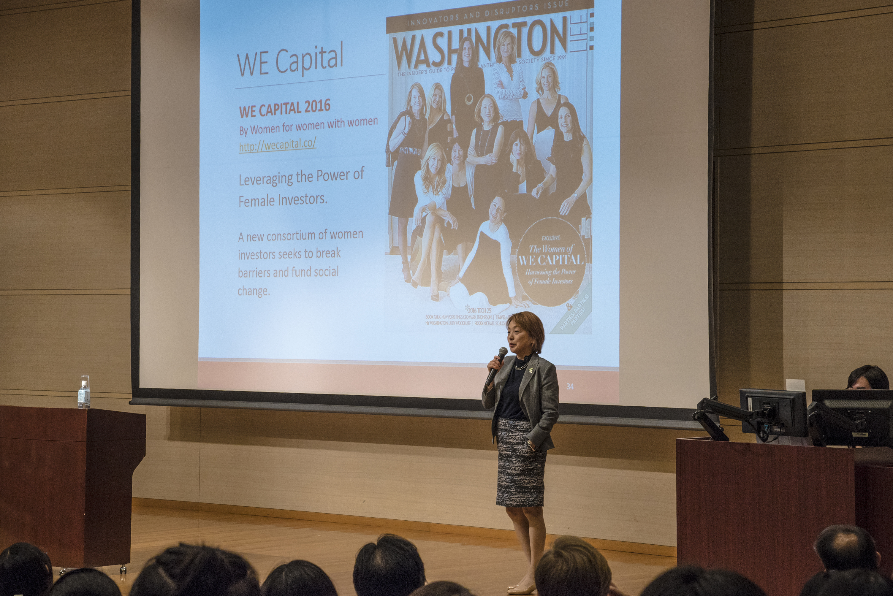 Dr. Kuno stands on stage. In the background is a slide of a front page of Washington magazine featuring Dr. Kuno