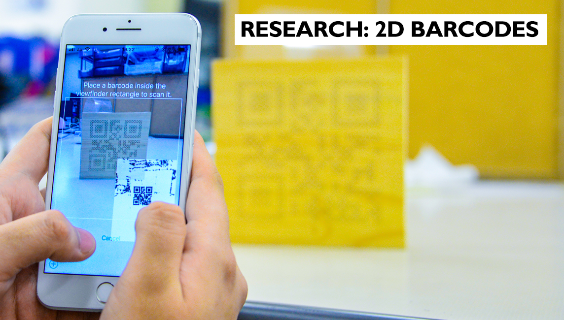 A smart phone takes a snapshot of a 2D Porous Code engraved onto a wooden surface - Research at Ristumeikan University