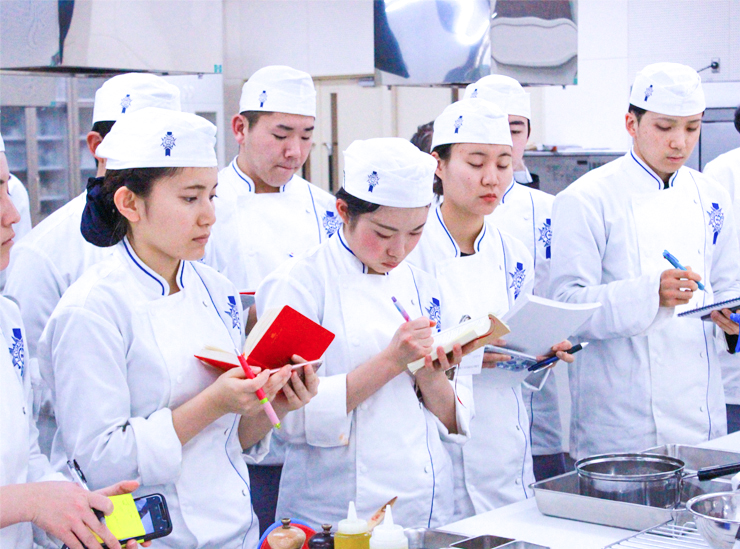 Ritsumeikan University students on the Global Culinary Arts and Management Programme take notes standing up wearing their chef's uniform