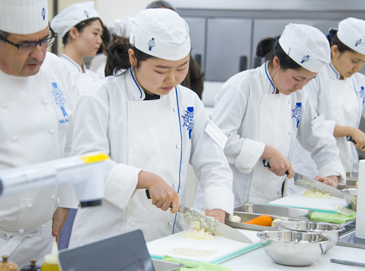 Ritsumeikan University College of Gastronomy Management students in chef whites concentrate intensely on chopping carrots and other vegetables to size under the watchful eye of Le Cordon Bleu Chef Gilles Company