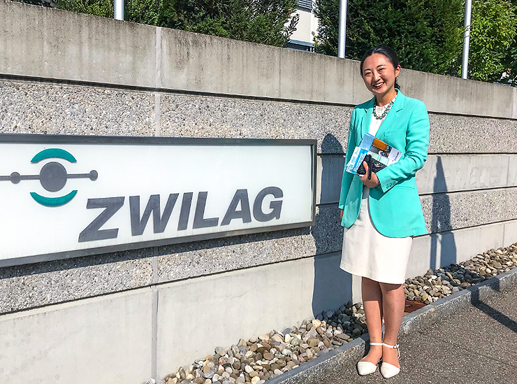 Professor Lim of Ritsumeikan University stands in front of the Zwilag sign in Switzerland holding related reference material under arm