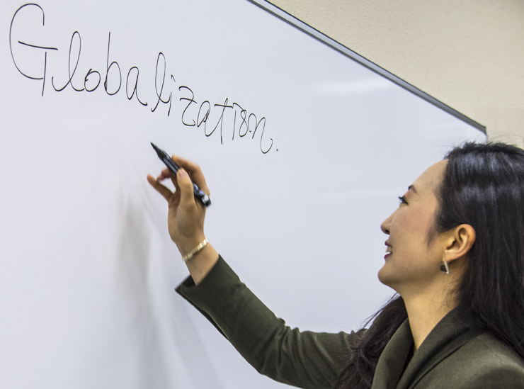 Ritsumeikan University's Professor Eujung Lim writes globalization on a whiteboard in black pen during a lecture