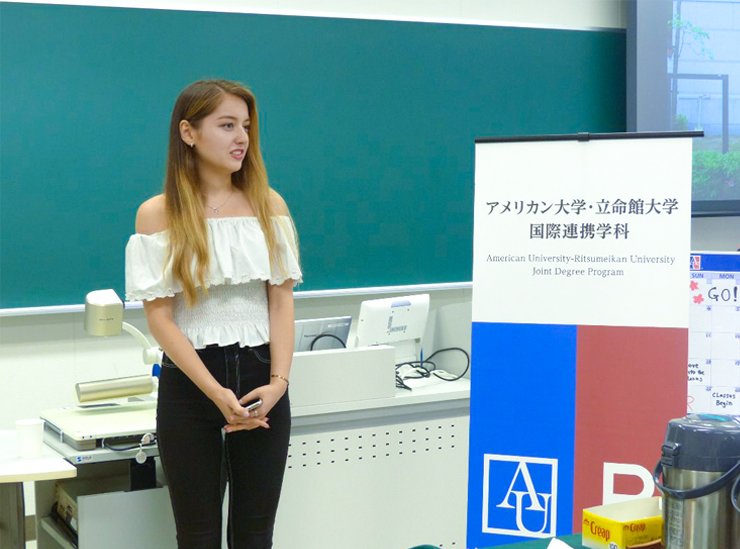 A Joint Degree Program student stands in a classroom giving her informal speech wearing a white top and black trousers, phone in hand, by a sign with the logos of RU and AU