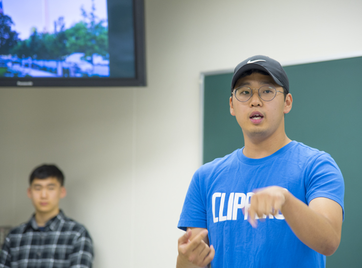 A Joint Degree Program student stands in a classroom giving his informal speech wearing a blue t-shirt, wearing a baseball cap, with a student looking on in the background