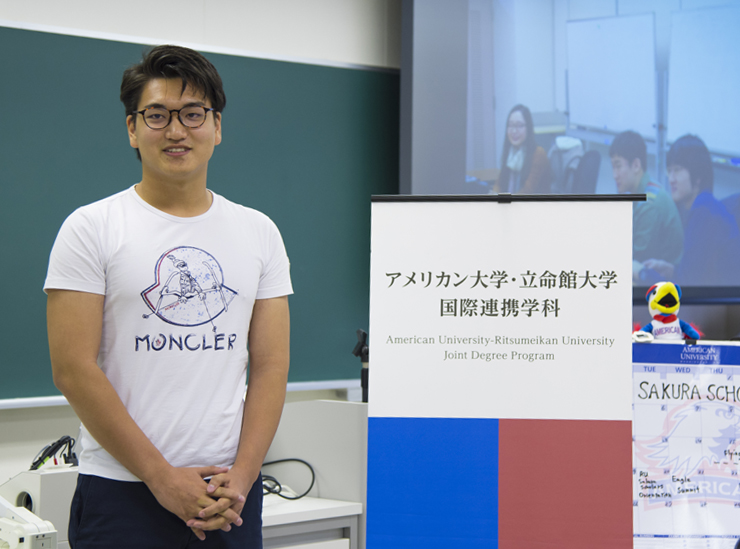 A Joint Degree Program student stands in a classroom giving his informal speech wearing a white t-shirt and black trousers, by a sign with the logos of RU and AU
