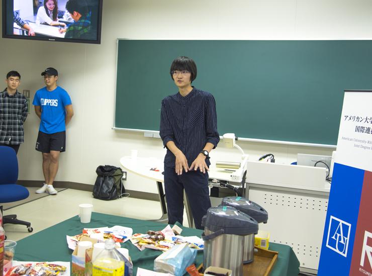 A Joint Degree Program student stands in a classroom giving his informal speech. The shot is zoomed out and so the table with refreshments on can be seen in the foreground. Two students listen in the background. The student himself is wearing a dark shirt with the sleeves rolled up and black trousers