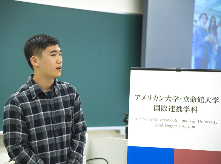 A Joint Degree Program student stands in a classroom giving his informal speech wearing a check black white and grey shirt.