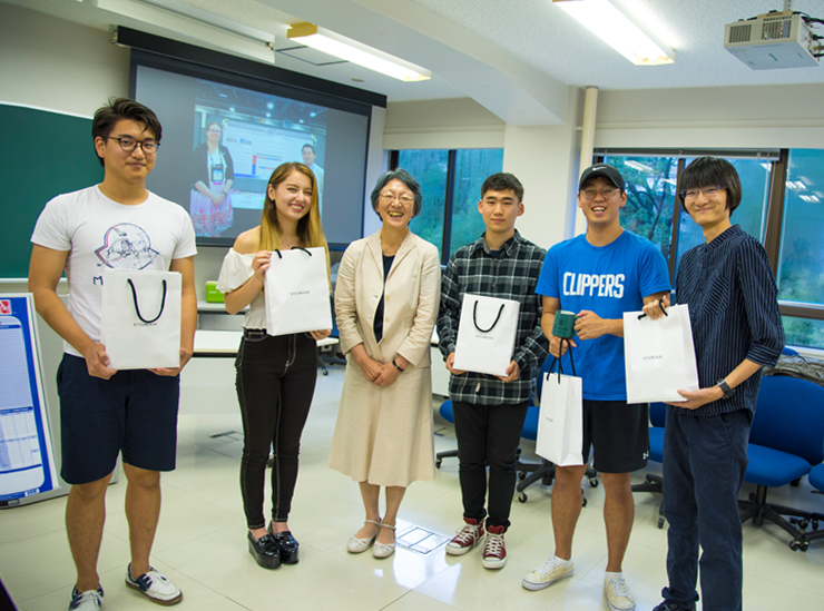 The five students stand with dean Kawamura. All are smiling and the students are holding their white send-off gift bags with black string handles and Ritsumeikan written across the front in small lettering