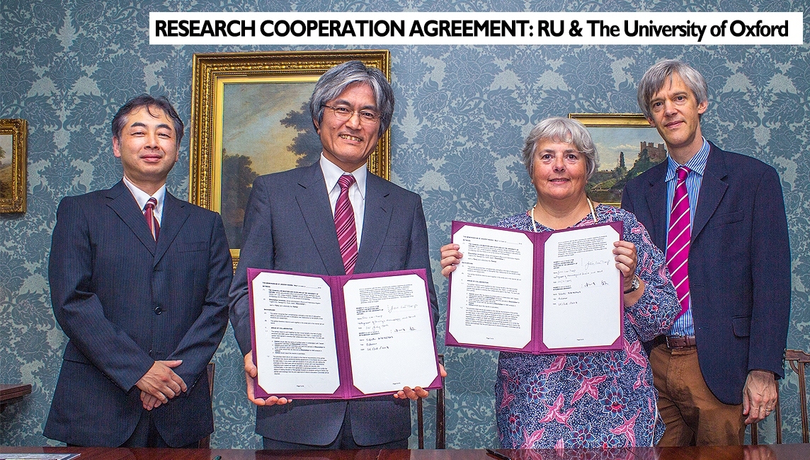 Agreement - Four leading research figures from Oxford and Ritsumeikan Universities pose in front of a wall decorated with old paintings and floral grasscloth wallpaper holding the signed agreements