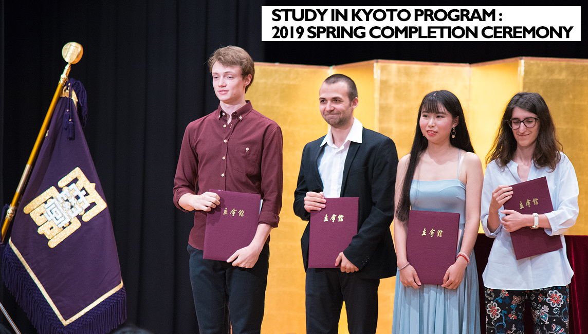 Four students of Ritsumeikan University's Study in Kyoto Program stand on stage, burgundy completion certificate binders under arm. To their left is the university flag. In the background is a Japanese gold-leaf gilded screen.
