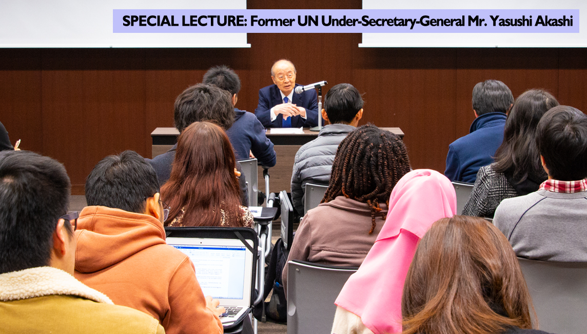 Former UN Under-Secretary-General Mr. Yasushi Akashi sits at a desk addressing a room full of students